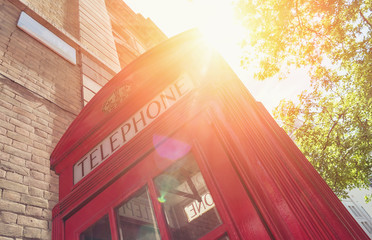 Fototapeta na wymiar Red Telephone Booth with sun at summer in London street