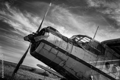 Fotografering  Old airplane on field in black and white