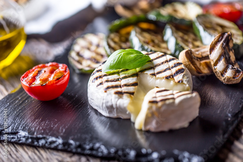 Camembert cheese. Grilled camembert cheese with zucchini tomatoes olive oil and basil leaves.
