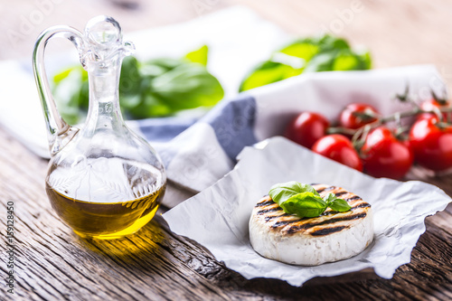 Camembert cheese. Grilled camembert cheese with olive oil and basil leaves.