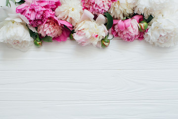 Obraz na Plexi Peonie White and pink peonies on a wooden background.