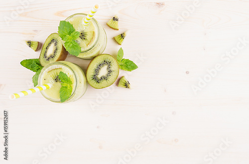 Foto op Canvas In het ijs Green kiwi fruit smoothie in glass jars with straw, mint leaf, cute ripe berry, top view. White wooden board background, decorative border, copy space.