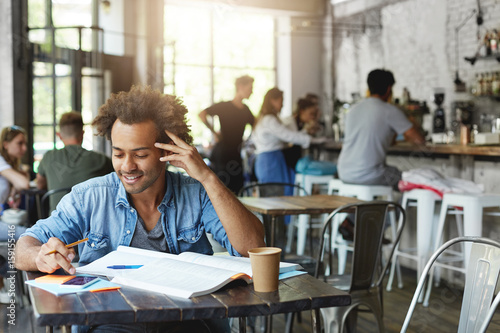 Fototapety, obrazy: Cheerful black student with stylish Afro haircut smiling broadly while reading message from his girlfriend on cell phone, browsing internet during lunch break while doing homework at coffee shop