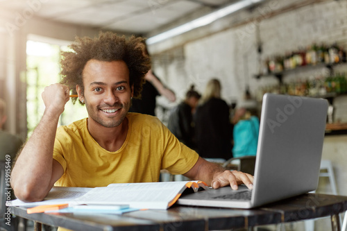 Foto Happy positive African American college student with cheerful cute smile using w