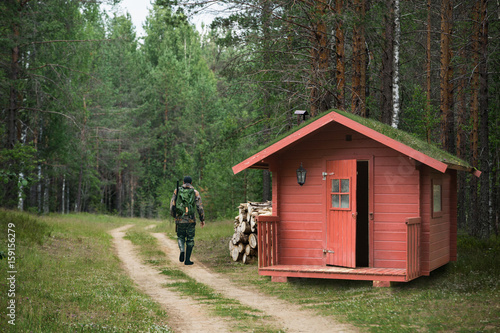 Foto op Aluminium Jacht Hunter with a gun went hunting from a red lodge with grass on the roof and walks along the forest road