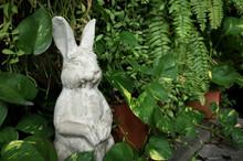 Rabbit Statue Among Tree And Plants