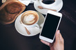Mockup image of hands holding white mobile phone with blank black screen with coffee cups on wooden table in restaurant