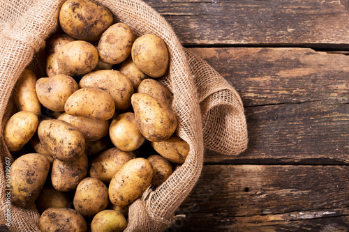 fresh potatoes in sack on wooden table Slika na platnu