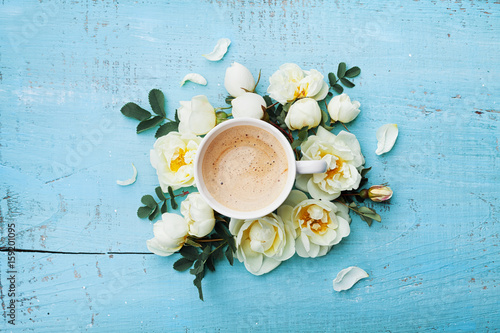 Fotografia Morning cup of coffee and beautiful roses flowers on turquoise rustic table top view