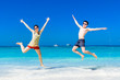 The happy Cheerful couple enjoys relaxing and jumping at white sand beach with blue sky and blue sea background.