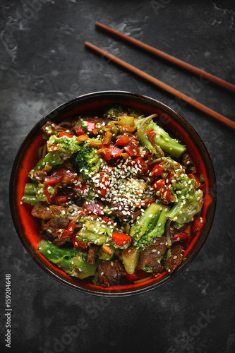 Photo  Noodles with vegetables and meat on a dark background, Asian food, Top view, Sel