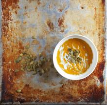 Colorful Pumpkin Soup And Pumpkin Seeds On An Old Baking Sheet, Selective Focus, Primitive Kitchenalia