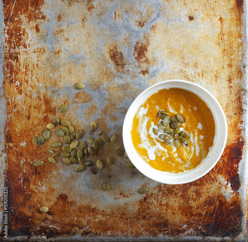 Valokuva  Colorful pumpkin soup and pumpkin seeds on an old baking sheet, Selective focus,