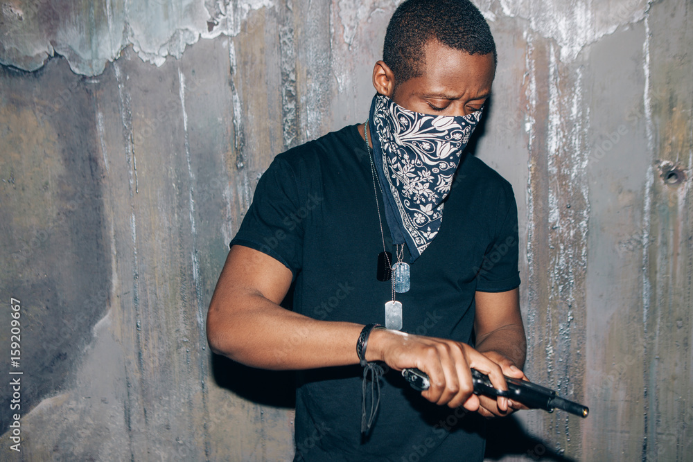 Fototapeta Black gang member checks his weapon. Gangster man with gun in hand on dark gray background. Outlaw, ghetto, murderer, armed attack concept