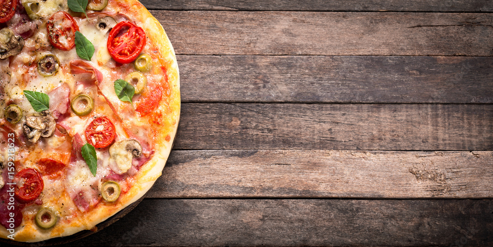 Pizza with ham and cheese on the wooden table