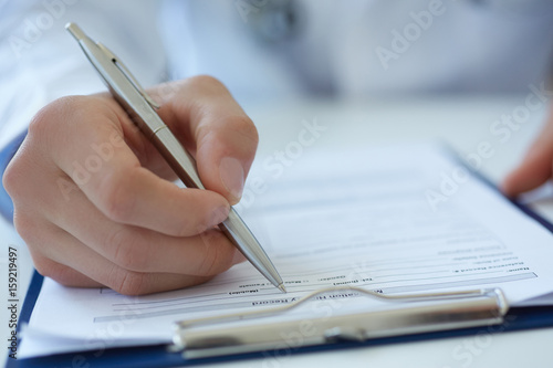Photo Close up of doctor's hands taking notes