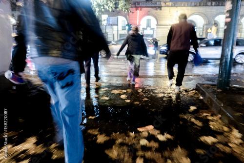 Foto  Pioggia di notte all'incrocio stradale con pedoni