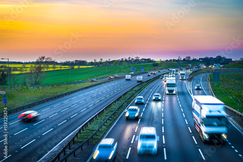 Fotografie, Obraz  Colourful sunset at M1 motorway near Flitwick junction with blurry cars in United Kingdom