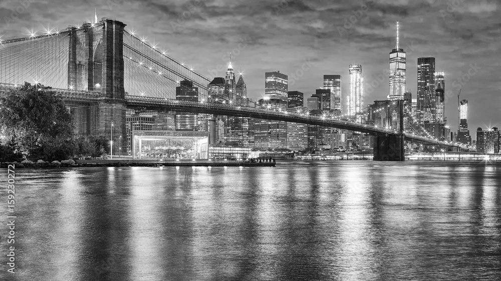 Fototapeta Black and white photo of Brooklyn Bridge and Manhattan at night, New York City, USA.