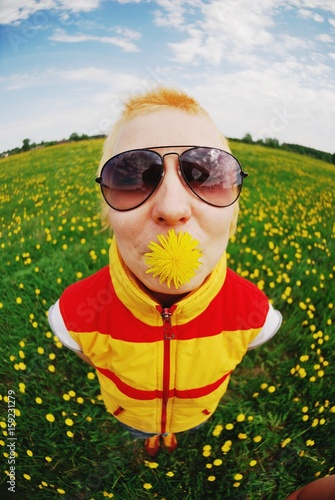 Fotografie, Obraz  Portrait of young beautiful girl with dandelion in sunglasses, enjoying the summer sun on a blossoming meadow