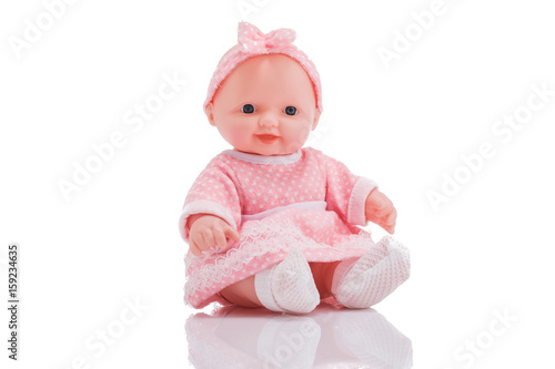 Cute little plastic baby doll with blue eyes sitting  isolated on white backgrou Fototapeta