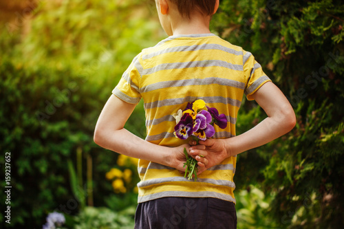Stickers pour porte Pansies Child hands holding a bouquet pansies flower . Back view.Focus for flowers