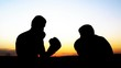 Boxing training outdoors. Opponents in boxing gloves silhouette sparring in field at sunset. Fighter deals a series of punches.