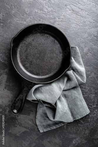 Empty cast iron frying pan on dark grey culinary background, view from above
