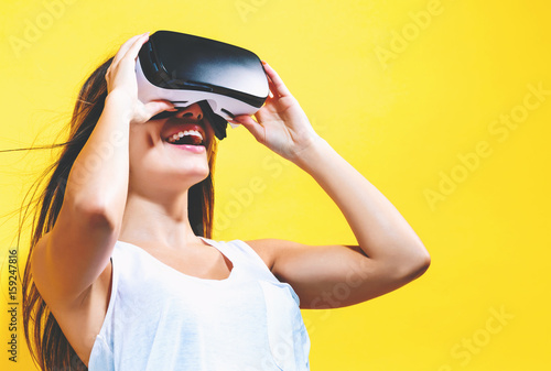 Fototapeta Young woman using virtual reality headset