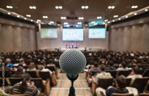 Fotografía  Microphone over the Abstract blurred photo of conference hall or seminar room wi