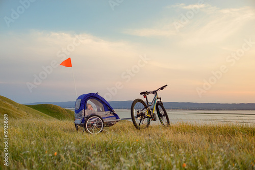Plagát  Biking in the hills at sunset with child trailer
