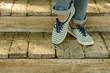 Female legs in blue jeans and striped sneakers on old wooden steps.