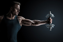 Male Bodybuilder Workout Pumping Up Muscles Holding Dumbbell Stretching Out His Hand. Strong Athlete With Perfect Deltoid Muscles, Shoulders, Biceps, Triceps And Chest.