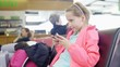 Little girl playing games on smartphone in airport departure area