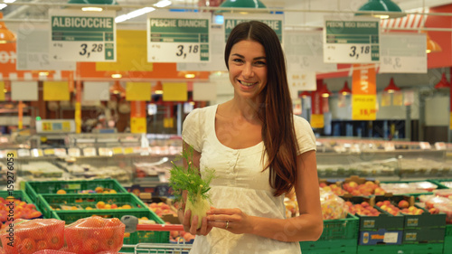 Keuken foto achterwand A beautiful young girl (woman) at the grocery store, in a white tank top, supermarket, chooses alcoholic drinks products, with a cart. Concept: buy products, large purchases, market, store, products.