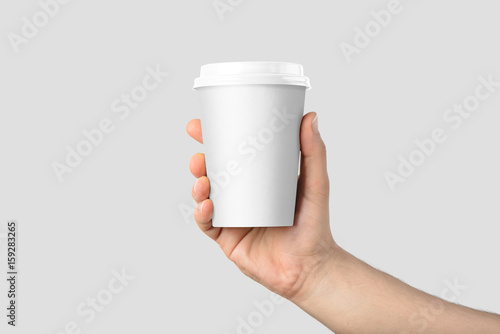 Obraz Mockup of male hand holding a Coffee paper cup isolated on light grey background.  - fototapety do salonu
