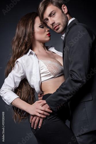 Plakat młoda namiętna para zakochanych obejmując i stanie pocałować odizolowane na czarno