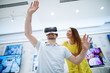Couple in electronics store, exploring VR goggles and having a good time.