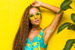 Leinwandbild Motiv Close-up of a beautiful young pretty girl on a yellow wall, in a turquoise overall with a print of bananas, leaves of a tropical plant, fashionable bright look, tanned bronze skin, summer vacation