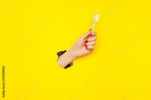 Photo  Crop hand with toothbrush in paper hole