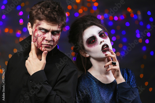 Young people in color contact lenses, with Halloween makeup at party Canvas Print