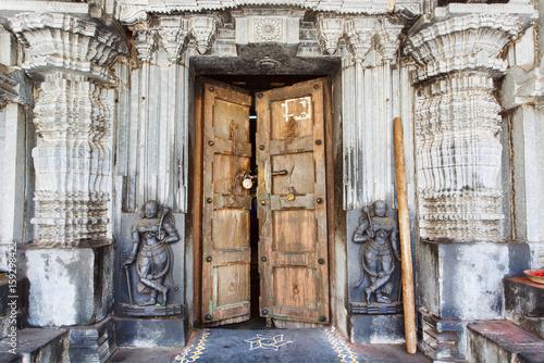 Wooden door in historical hindu temple with stone walls collumns