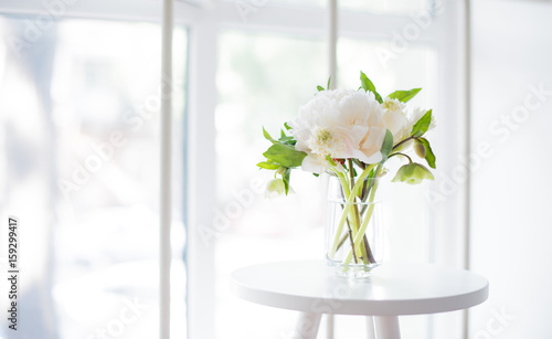 Fotografía  white peony flowers on coffee table in white room interior, brig