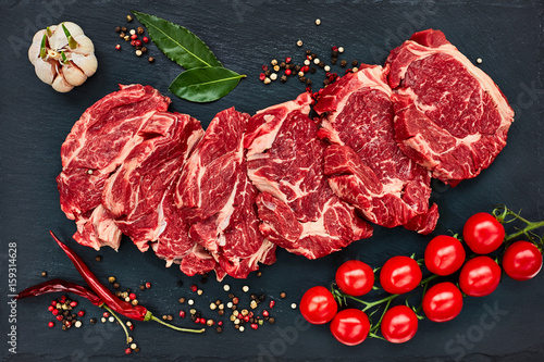 Fresh raw beef steaks with pepper and tomatoes on black slate board Wallpaper Mural
