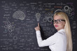 Business woman and formula on the blackboard