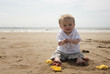 One year old baby boy playing with sand on the beach