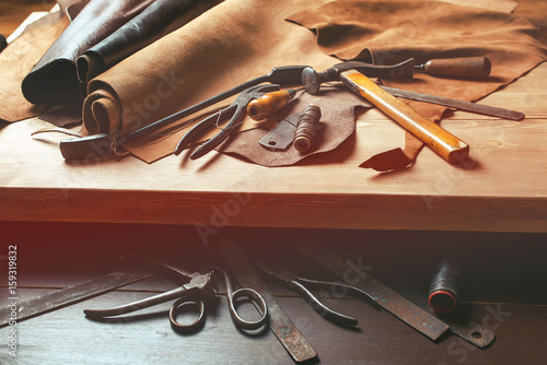 Photo  Cobbler tools in workshop on the wooden table . Top view.