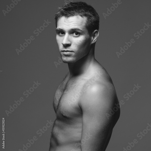 c4e603e977d Bodybuilding and body sculpture concept. Beautiful (handsome) muscular male  model with perfect body posing over blue background. Black and white studio  shot