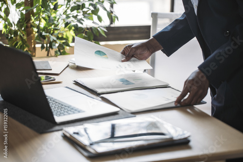 Hands of cropped unrecognisable African businessman standing at office and holding papers.