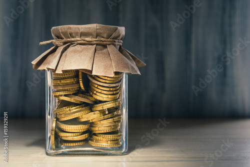 Photo Euro coins in glass container over wooden background